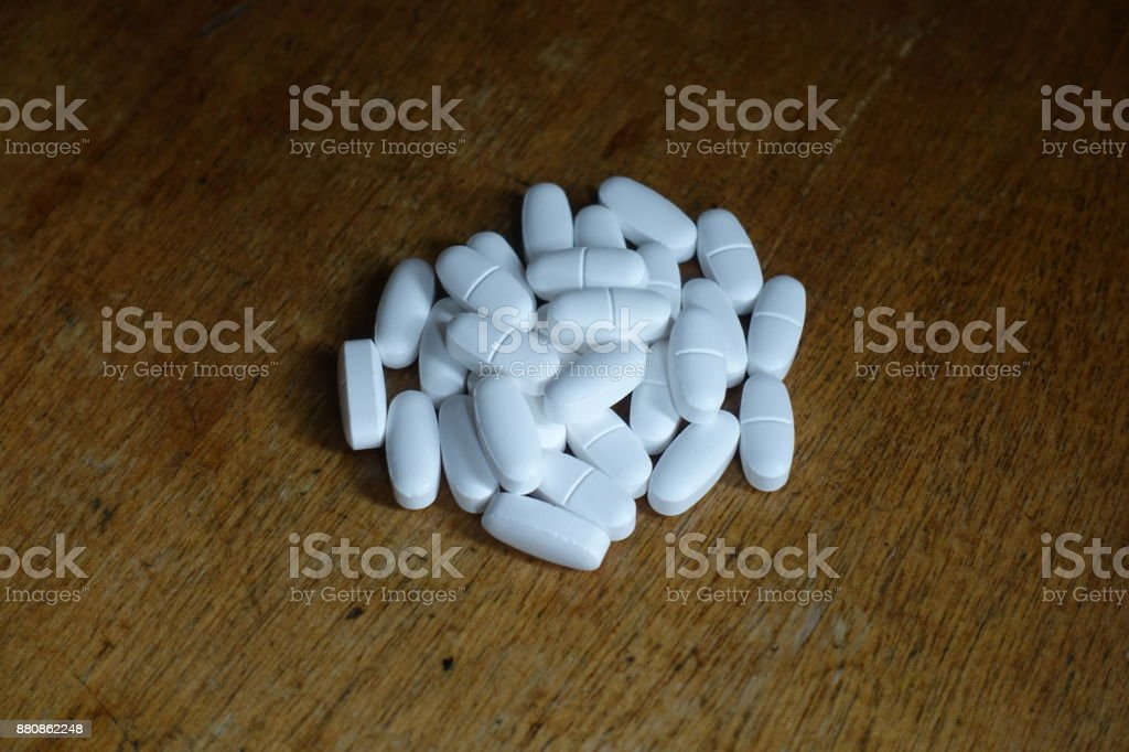 Fistful of white oblong tablets of calcium citrate stock photo