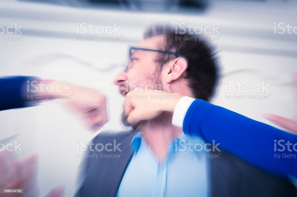 Fists punching businessman in the face stock photo