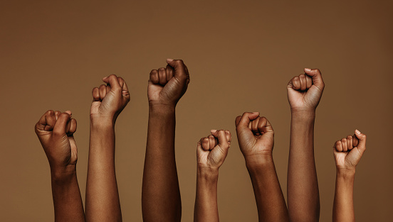 Cropped shot of hands raised with closed fists. Multiple hands raised up with closed fist symbolizing the protests movement.