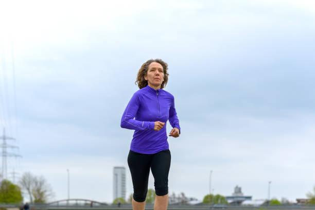 fit active woman running against a cloudy sky - carpet runner stock photos and pictures