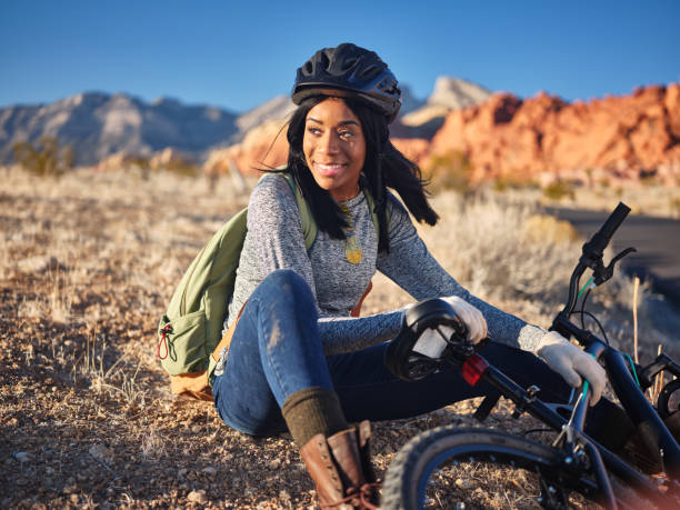 fit african american woman stopping to take a rest beside bike stock photo