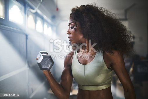 930998708 istock photo fit african american woman working out by lifting weights in home gym 930999516
