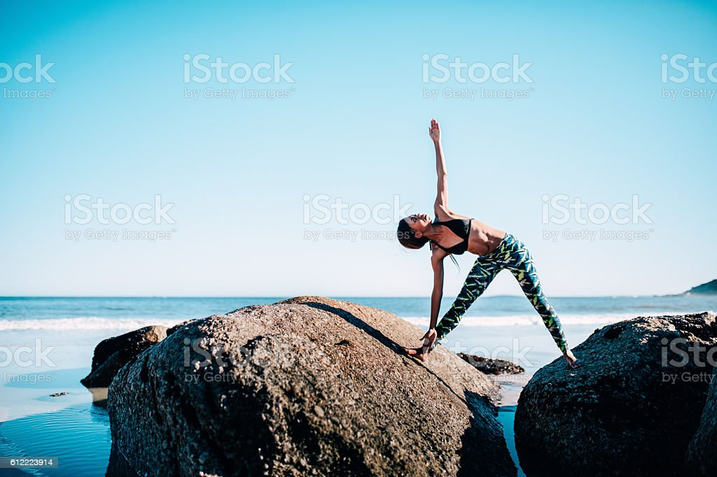 Fit african woman doing yoga exercise on rocks by the stock photo