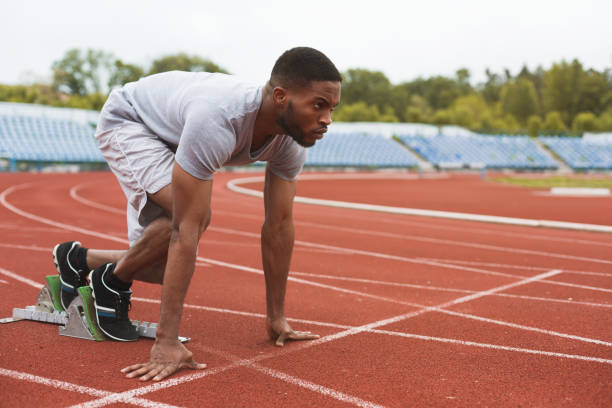 Fit afro-american runner in starting position on stadium Fit afro-american sportsman on starting position, ready to run at the stadium male likeness stock pictures, royalty-free photos & images