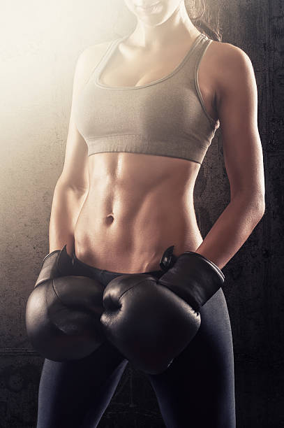 Fit and attractive girl with boxing gloves in training stock photo
