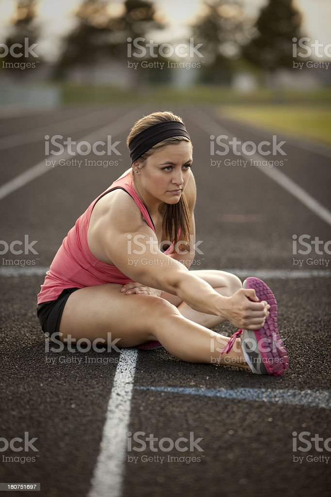 Fit and attractive woman stretching on a track. royalty-free stock photo