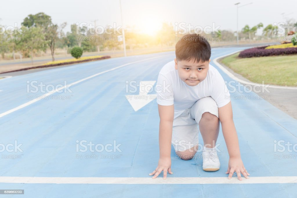 fit and confident boy in starting position ready for running stock photo
