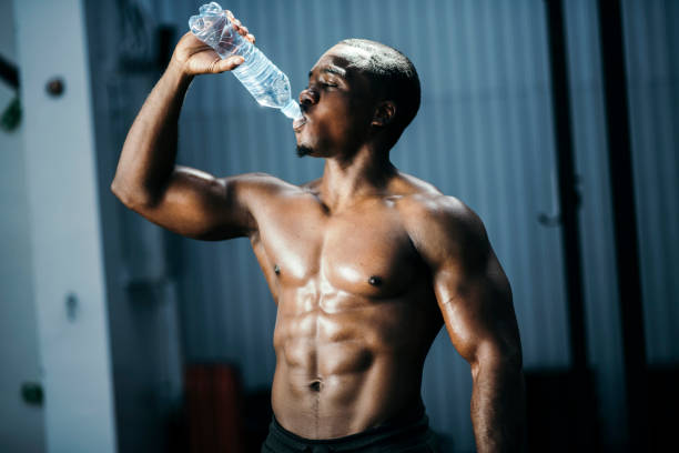 Fit and mascular man drinking water stock photo