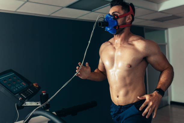 Fit and muscular athlete with mask running on treadmill stock photo