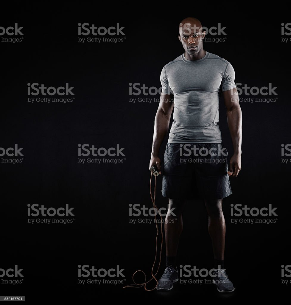 Fit and muscular man with jumping rope stock photo