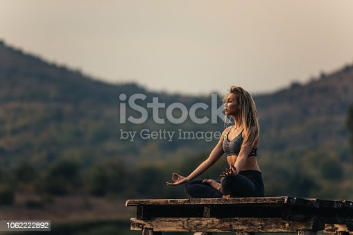 Fit and sporty young woman doing yoga next to the lake