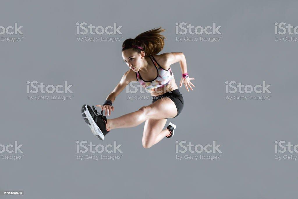 Zinde ve sportif genç kadın beyaz arka plan üzerinde atlama. royalty-free stock photo