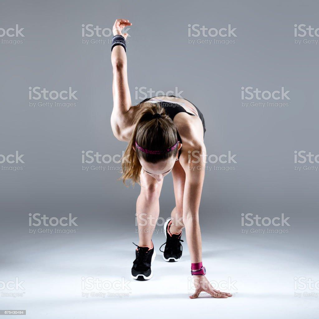 Forme et sportive jeune femme prépare pour une course sur fond blanc. photo libre de droits