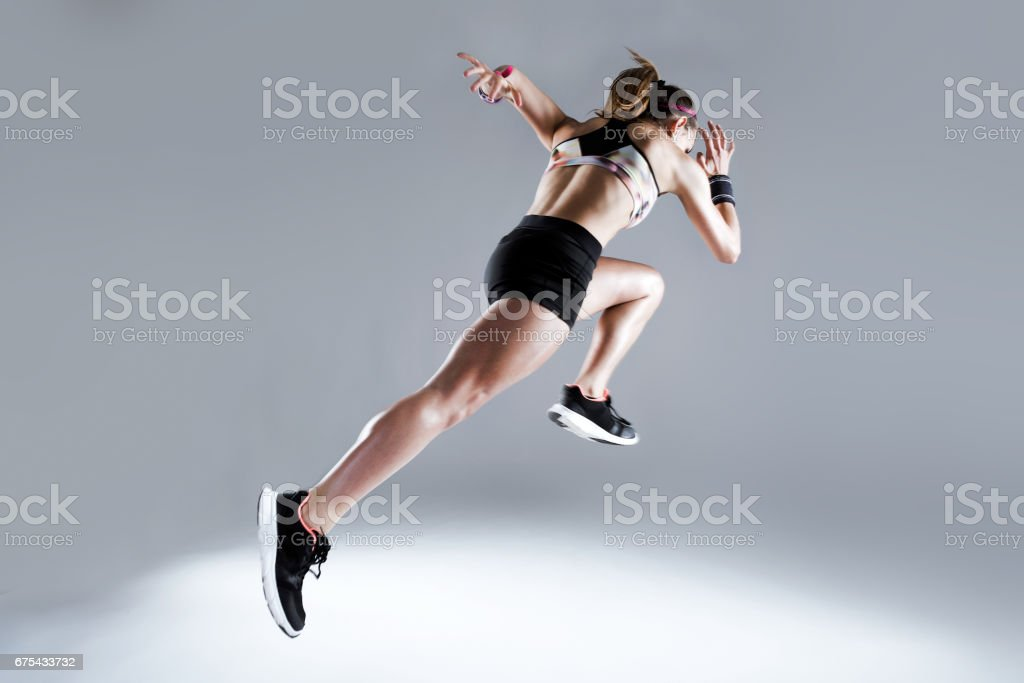 Fit and sporty young woman running on white background. stock photo
