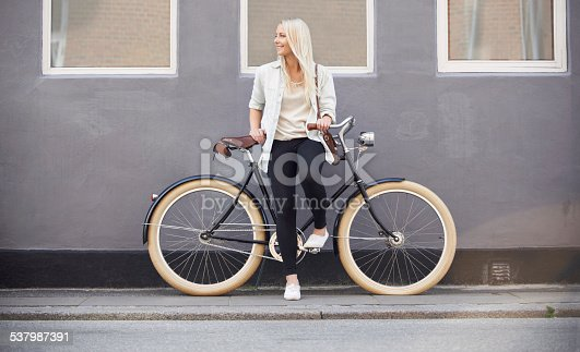 A beautiful young woman leaning on her bike on the side of the street