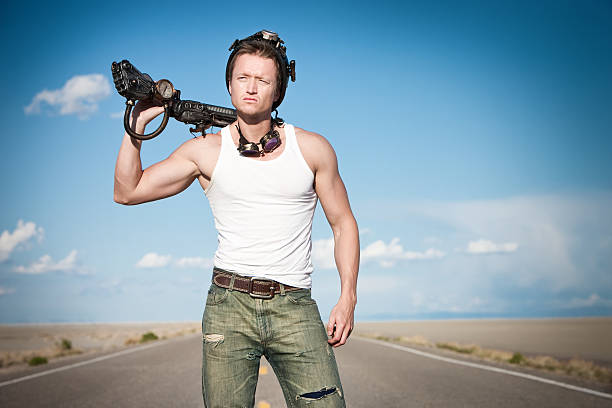 Fit Apocalyptic Survivalist Portrait of athletically built young male resting his modified weapon on his shoulder in the middle of desolate roadway and wasteland.  He looks off camera with hardened countenance. adversarial stock pictures, royalty-free photos & images