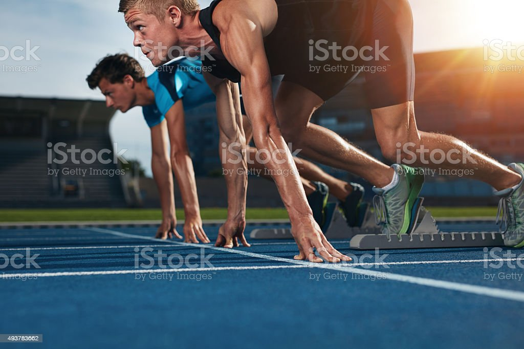 Fit athlete running race in athletics racetrack Two young athletes at starting position ready to start a race. Sprinters ready for race on racetrack with sun flare. 2015 Stock Photo