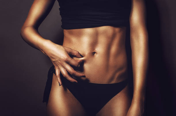 Fit athletic woman pinching her stomach skin showing perfectly shaped abs and body with no cellulite stock photo
