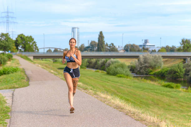 Fit athletic woman running on a country road stock photo