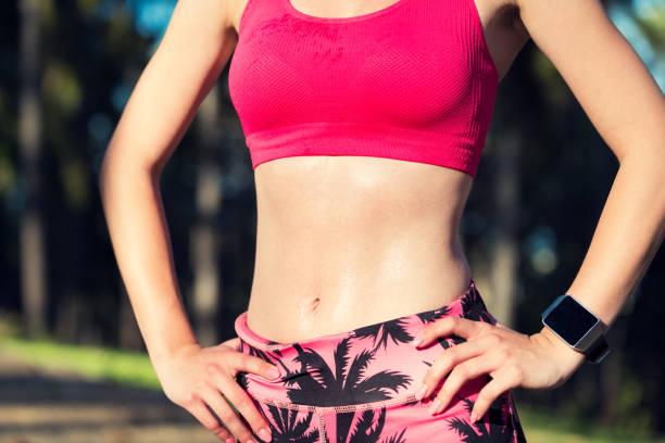 monter une femme athlétique, prenant une pause de la séance d'entraînement intense. - brassière de sport photos et images de collection