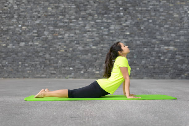 Fit athletic young woman doing yoga exercises Fit athletic young woman doing yoga exercises stretching and arching her back with raised arms in a profile view on a mat in front of the wall of an urban building with copy space cobra pose stock pictures, royalty-free photos & images