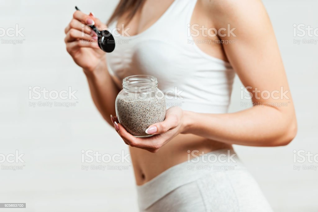 Fit, attractive woman holding a glass jar of chia pudding stock photo