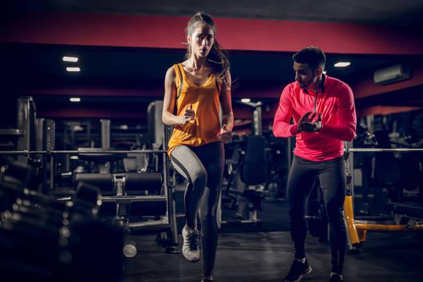 forma hermosa chica centrada calentando en un gimnasio con su entrenador personal, por su lado. - entrenador personal fotografías e imágenes de stock