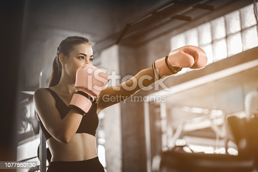 istock Fit beautiful woman boxer hitting a huge punching bag exercise class in a gym. Boxer woman making direct hit dynamic movement. Healthy, sports, lifestyle, Fitness, workout concept. With copy space. 1077550130