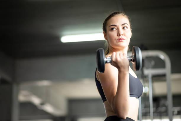 Güzel genç kadın beyaz spor giyim kameraya poz uygun. Bir spor salonunda bir egzersiz dersi sırasında halter tutan genç kadın. Sağlıklı spor yaşam tarzı, Fitness kavramı. stok fotoğrafı