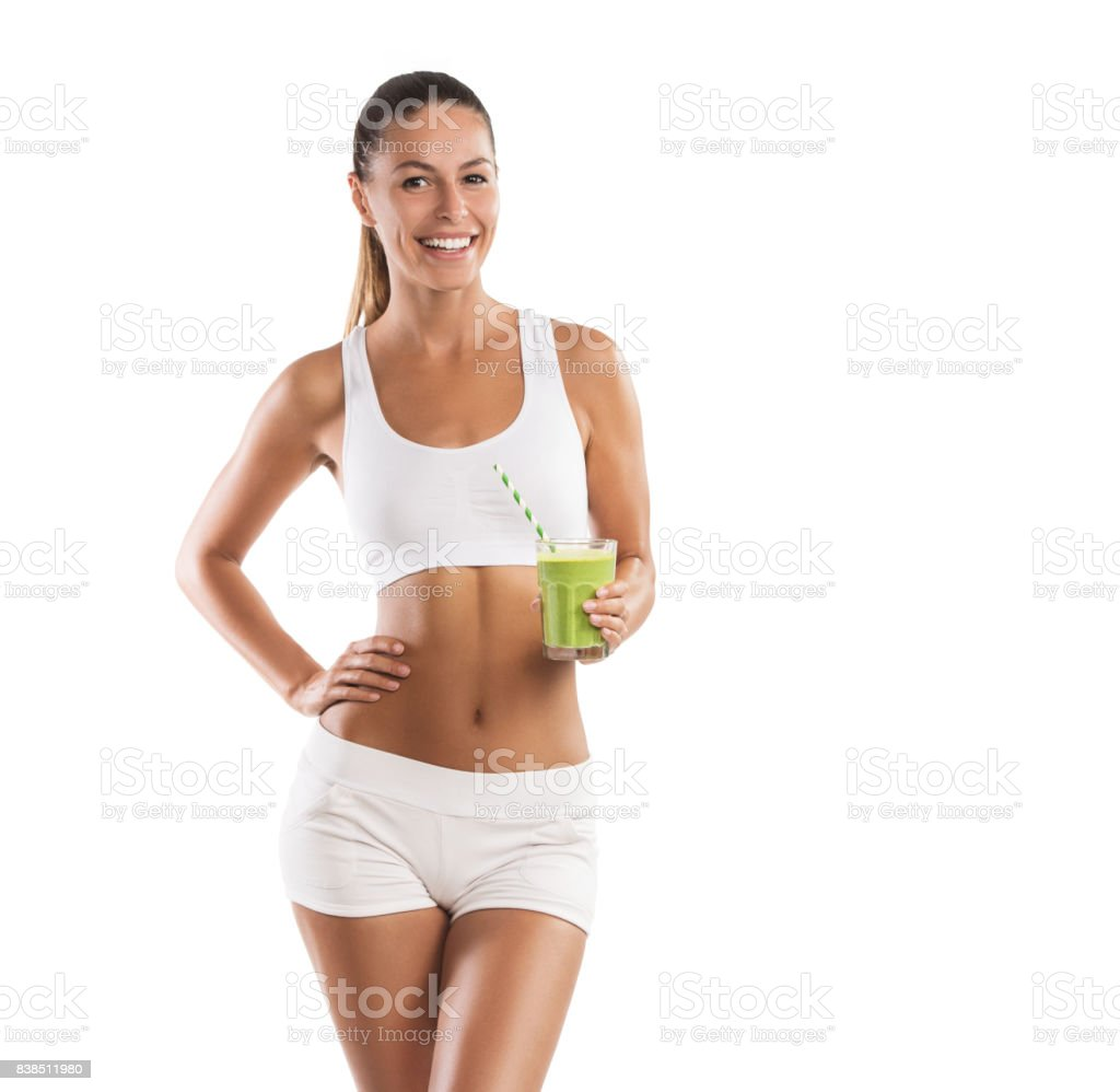 Fit, beautiful, young woman holding a healthy, green smoothie, isolated on white background stock photo