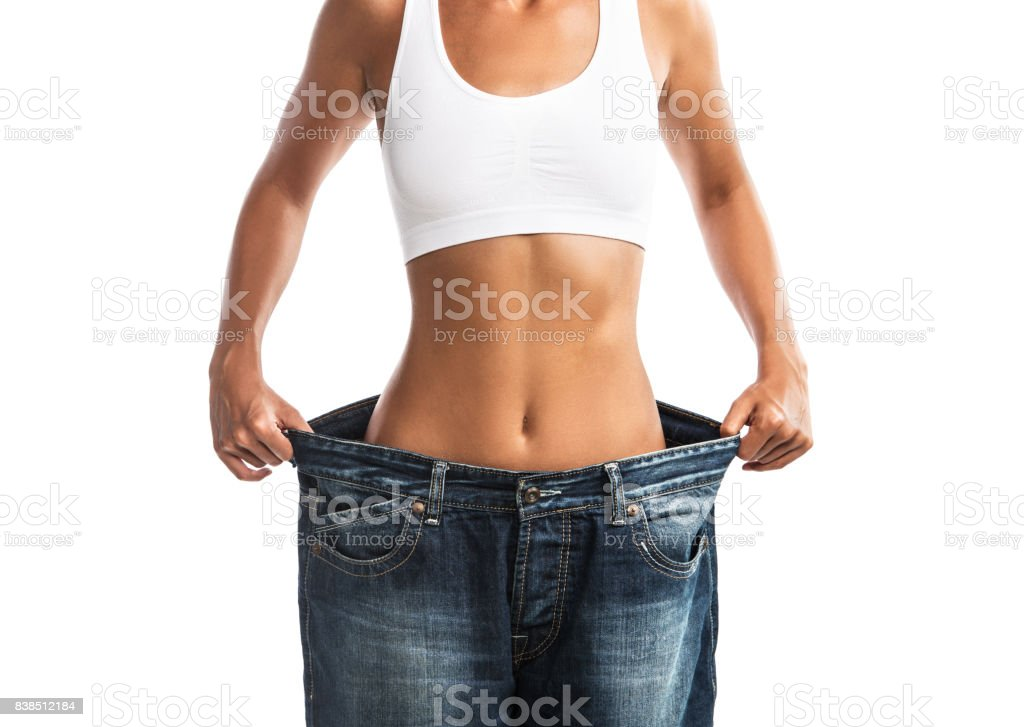 Fit, beautiful, young woman in oversize pants, isolated on white background stock photo