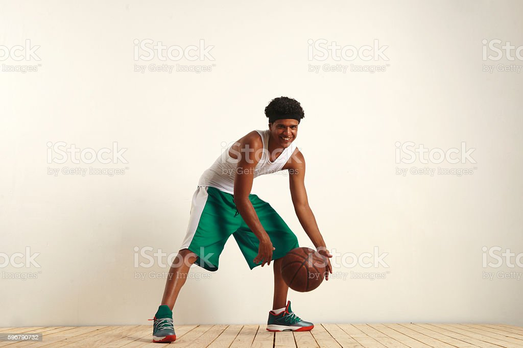 Fit black athlete playing with a vintage basketball stock photo