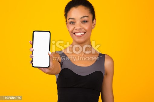 1159261513 istock photo Fit Black Girl Showing Phone Blank Screen Standing, Yellow Background 1192084270