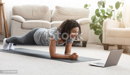 Training At Home. Fit black woman doing yoga plank while watching online tutorial on laptop, exercising in living room, free space, panorama
