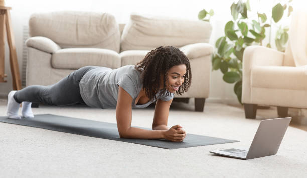 Fit black woman training at home, watching online tutorial on laptop stock photo