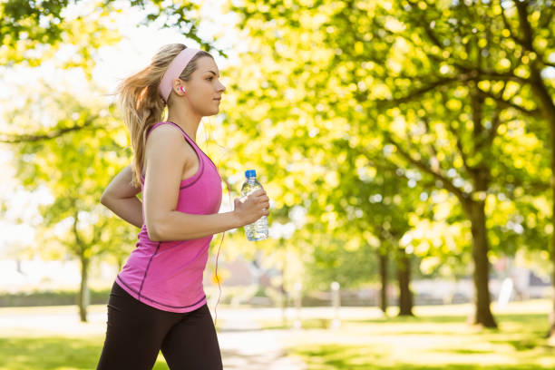 Fit blonde jogging in the park stock photo