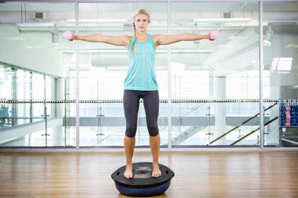 Fit blonde standing on bosu ball and lifting dumbbells stock photo