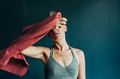 Woman in sportswear playing around with a red towel.
