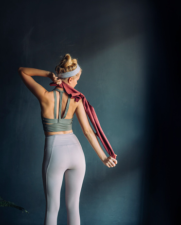 Woman in sportswear playing around with a red towel at home - back view