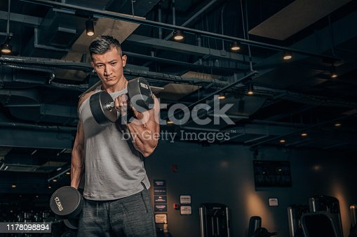 One Chinese man, training with dumbbell alone in dark gym.