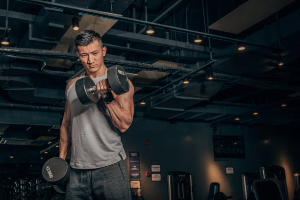 Fit Chinese guy practicing with dumbbells in gym One Chinese man, training with dumbbell alone in dark gym. training equipment stock pictures, royalty-free photos & images