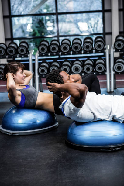 Fit couple doing bosu ball exercises stock photo