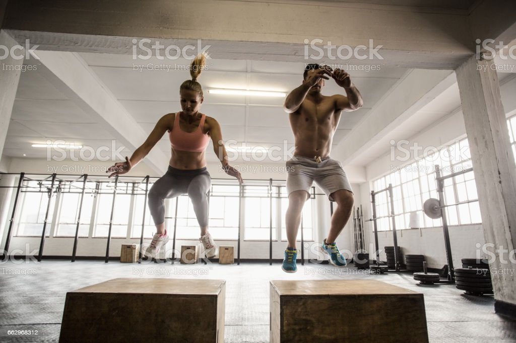 Fit couple doing set of box jumps stock photo