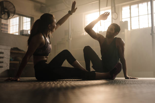 fit couple high five after workout in health club - allenatore foto e immagini stock