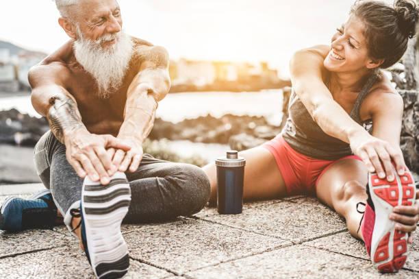 fit machen, dehnen vor dem training laufen paar - jogger im freien training bei sonnenuntergang zusammen - main konzentrieren sich auf womaman gesicht - fitness, sport, wellness, training, fitness-studio und gesunden lifestyle-konzept - laufende tattoos stock-fotos und bilder