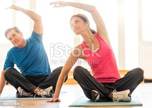 istock Fit couple practicing yoga on mat at home 469757806