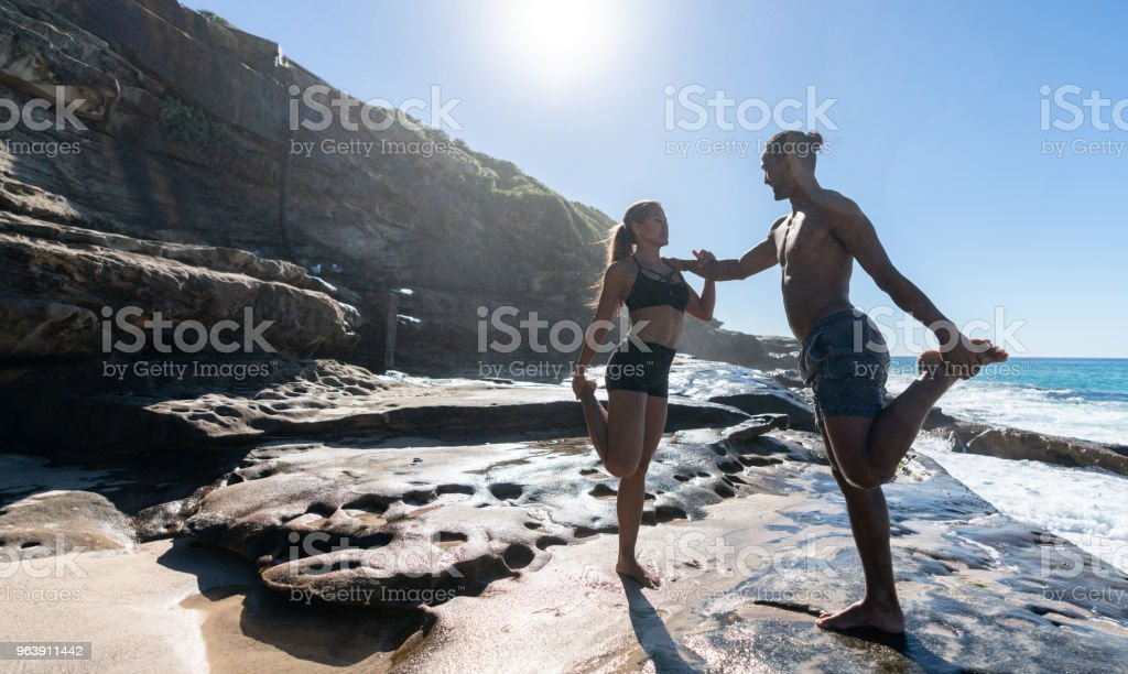 Fit couple stretching together at the beach - Royalty-free Adult Stock Photo