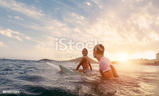 istock Fit couple surfing at sunset - Surfers friends having fun inside ocean - Extreme sport and vacation concept - Focus on man head - Original sun color tones 884657044