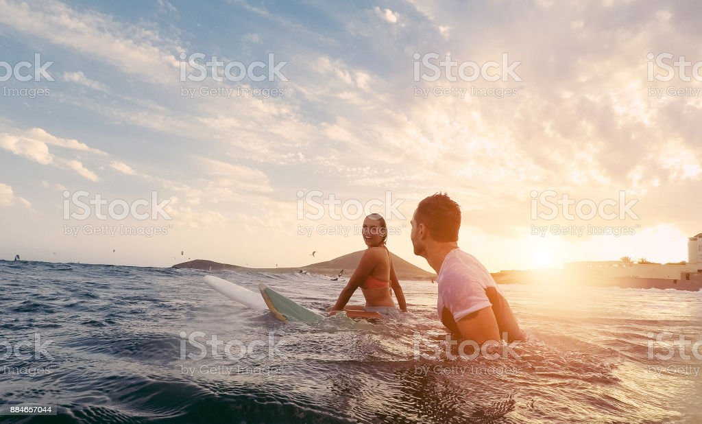 Fit couple surfing at sunset - Surfers friends having fun inside ocean - Extreme sport and vacation concept - Focus on man head - Original sun color tones stock photo