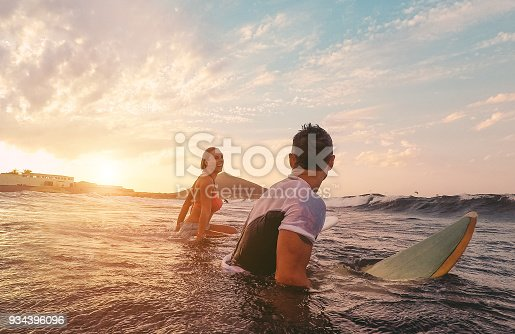 istock Fit couple surfing at sunset - Surfers friends having fun inside ocean - Extreme sport, travel, healthy lifestyle and vacation concept - Focus on man head 934396096